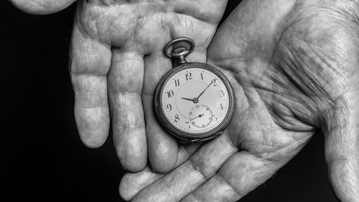 Old man holding a pocket watch