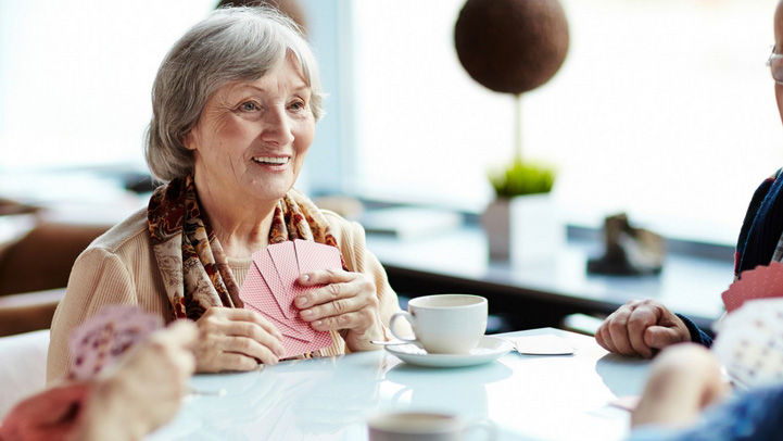 A senior woman playing cards with her friends