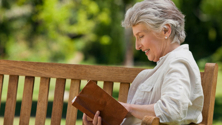 A senior woman reading her book on a park bench