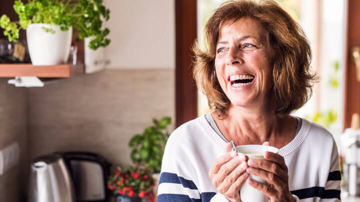 A senior woman laughing in her kitchen