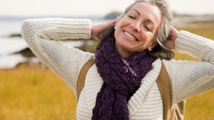 A happy woman hiking by a coastal line