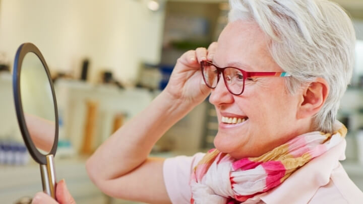A senior woman checking her new seeing glasses in the mirror