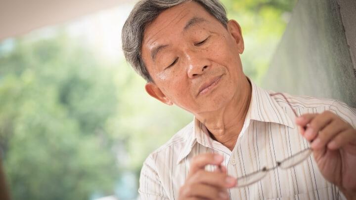 Older man looking at his seeing glasses