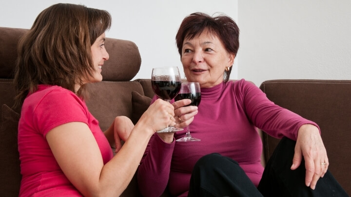 Mother and adult daughter enjoying some wine at home