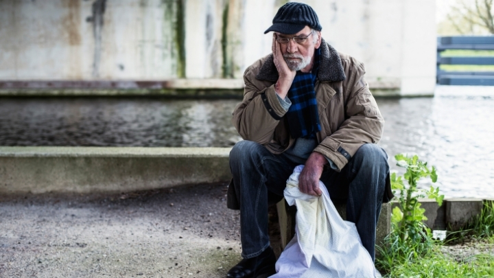 Old thoughtful homeless man