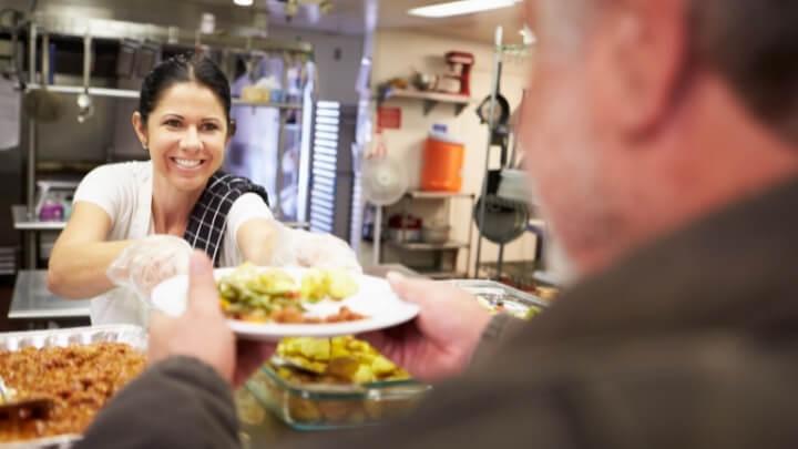 A woman serves food to a man