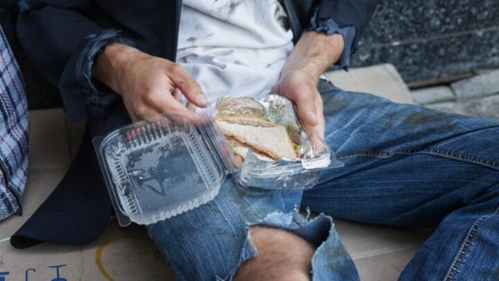 Homeless man eating donated sandwich