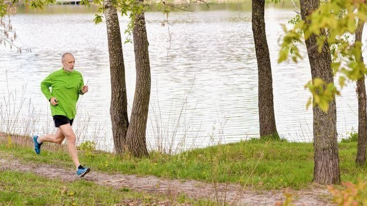 Older man jogging by a lake