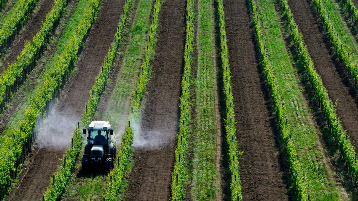 A tractor spraying pesticide on a field