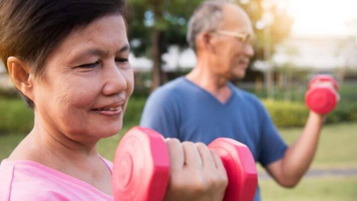 A senior couple working with dumbbells at the park