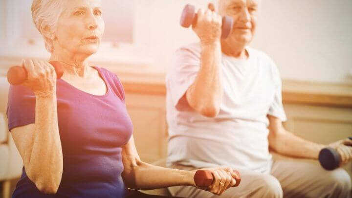 A senior couple working with dumbbells at home