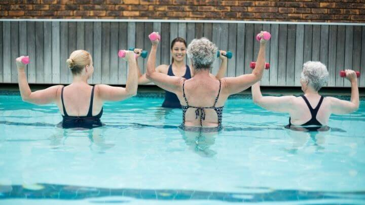 A group of senior women strenth train in the pool with an instructor