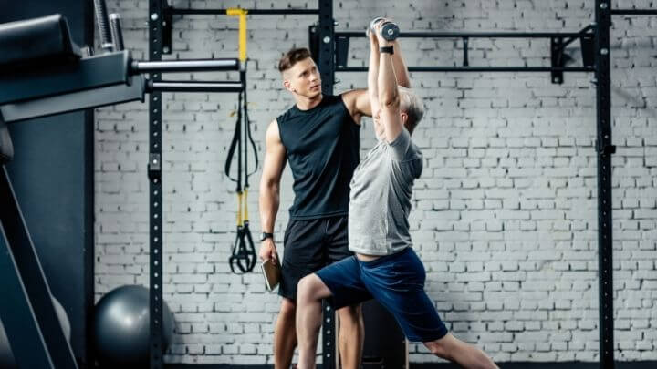 A middle-aged man works out at the gym with a trainer