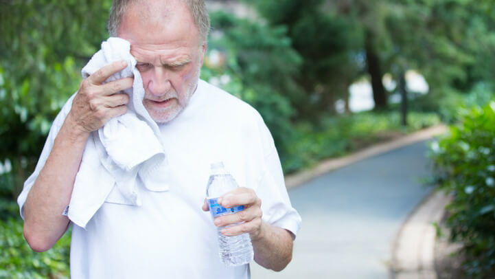 A sweaty senior man after exercise with a bottle of water
