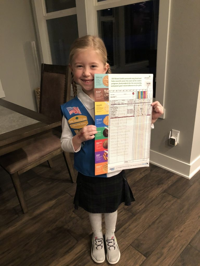 Girl holding her girl scout cookie orders