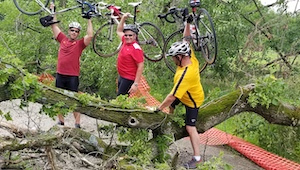 Three Two Rivers Marketing associates carry their bikes over a fallen tree on a bike trail
