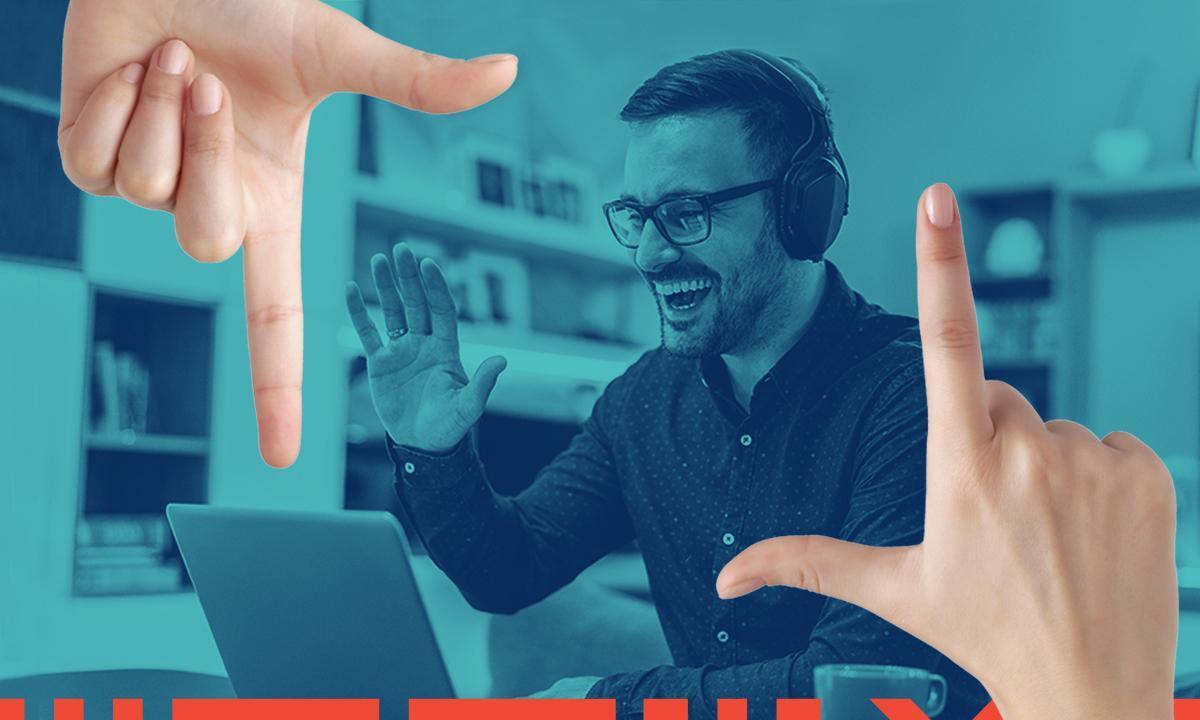finger framing a man on laptop