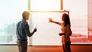 Man and woman standing discussing plans in front of a white board