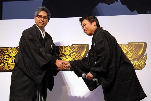 壇上で固い握手を交わすサンセイR&D執行役員 営業本部長・長谷川氏(右)と、サミー 代表取締役常務・星野氏(左)