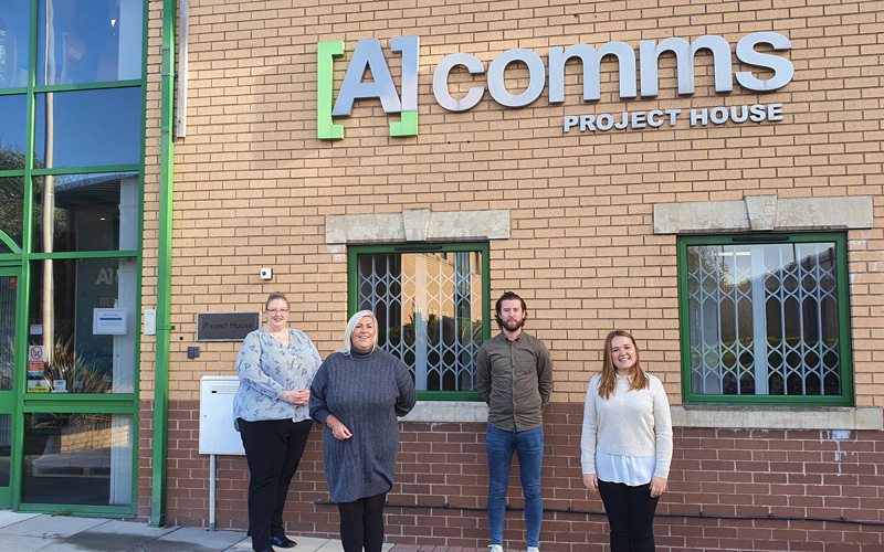 Four business employees stand in front of A1 Comms office building