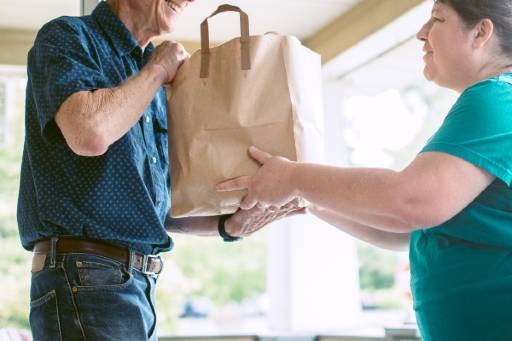 Senior man being handed a bag of groceries by a woman