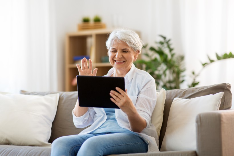 senior woman video chatting her loved ones on a tablet