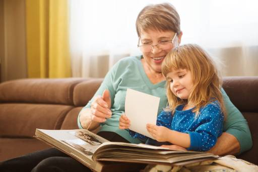 grandparent looking at a photo album with her granddaughter