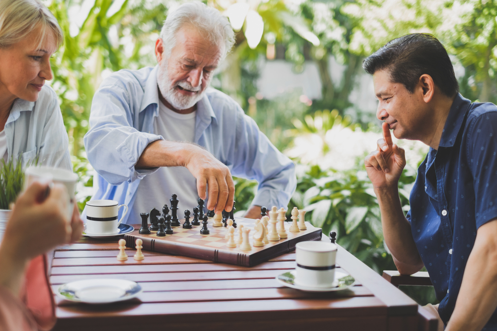 Seniors playing chess together outside
