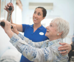 a senior woman working out with the assistance of a nurse at her senior living community