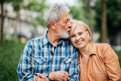 senior man kissing his wife on her head as she smiles at the camera