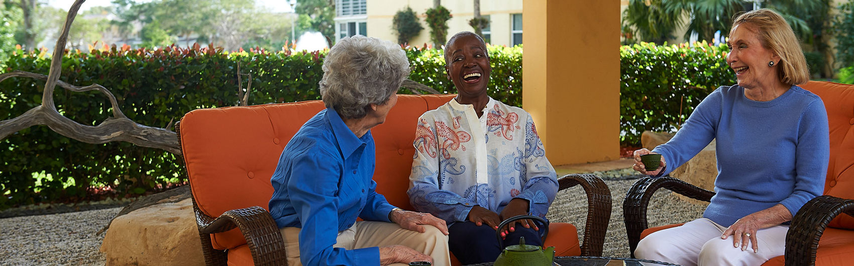 Three ladies chatting while sitting outside of their Delray Beach retirement community