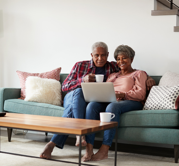 Senior couple on a couch looking at a laptop