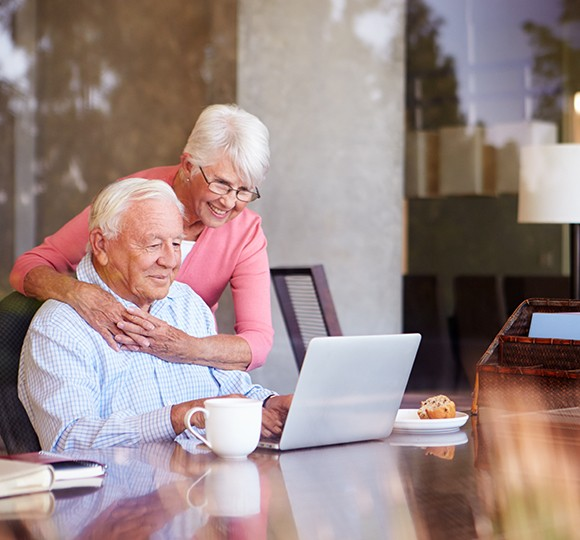 elderly woman hugging her husband while he looks at his laptop screen