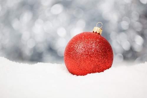 Pallina rossa per albero di Natale in mezzo alla neve