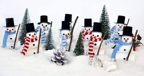 Squadra di pupazzi neve tra addobbi pini e pigne