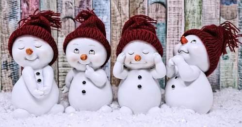 Bellissimi pupazzi di neve con berrettini di lana rossi