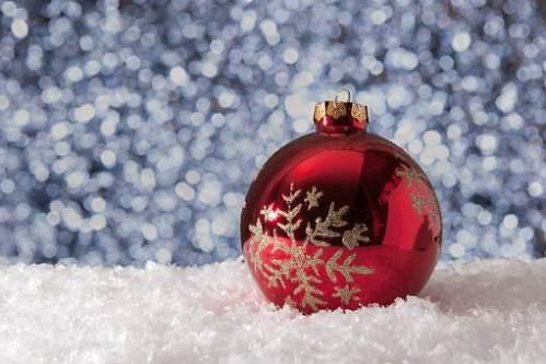 Pallina di Natale rossa sopra neve artificiale