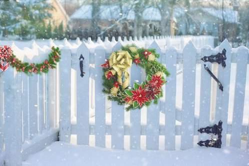 Recinto in legno con ghrilande e corone natalizie sotto la neve