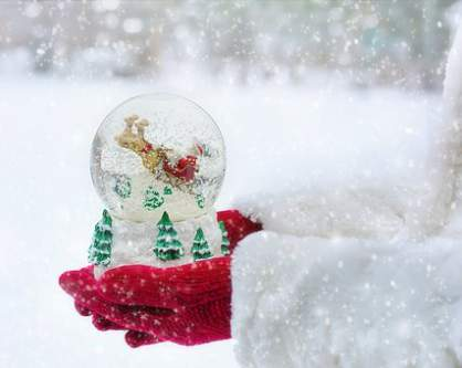 Sfera di cristallo natalizia innevata tra due mani