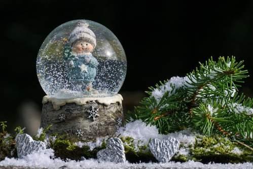 Dolce bambino in una sfera di cristallo con la neve che cade