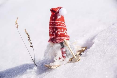 Simpatico babbo natale con berretto rosso scia sulla neve