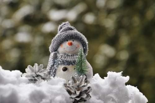 Pupazzo di neve con berretto su neve artificiale