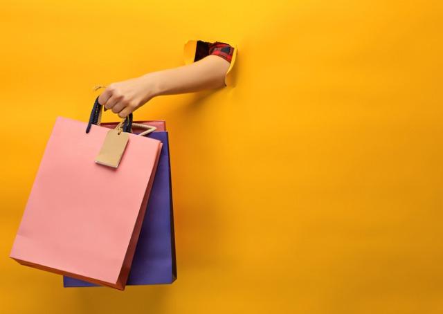 Experiência do consumidor - Mão com sacola de compra saindo de buraco na parede