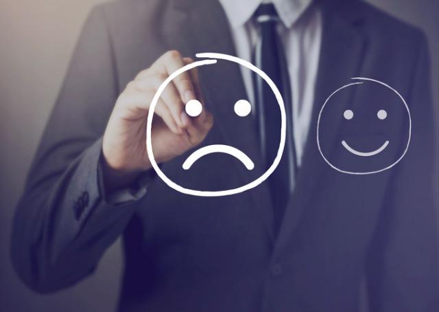 clientes difíceis - Homem desenhando em lousa transparente rostos de clientes feliz e infeliz