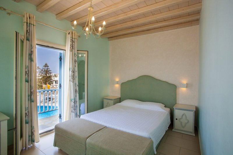 The interior of the room with the double bed, the bedside tables and the balcony with the view of the sea