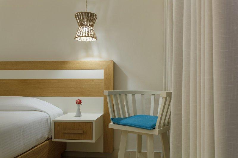 Το εσωτερικό του δωματίου με την καρέκλα και την άκρη του κρεβατιού