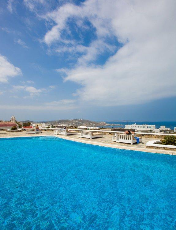 Η πισίνα στο Sunset Wing με τις ξαπλώστρες και επισκέπτες να απολαμβάνουν την θέα της Μυκόνου