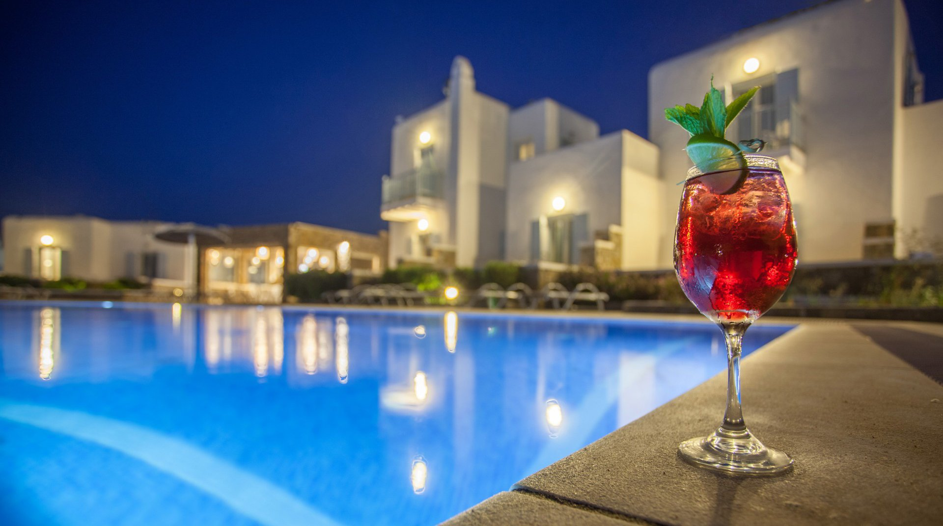 The pool of the Sunset Wing during night time with a cocktail and the restaurant in the background