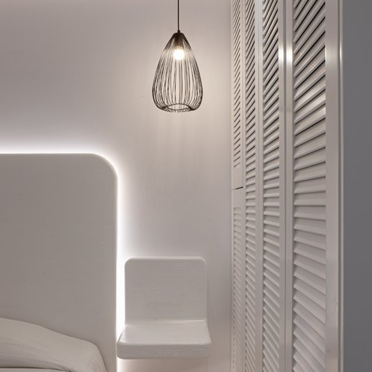Το εσωτερικό του δωματίου από την μία πλευρά, με το κρεβάτι, το κομοδίνο, το φωτιστικό και την ντουλάπα