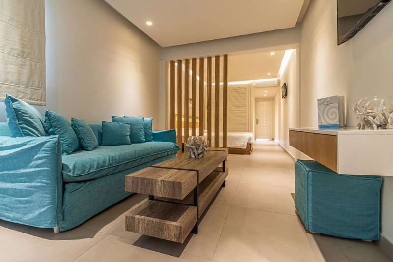 The sofa of the suite, with the coffee table and the bed with the closet in the background